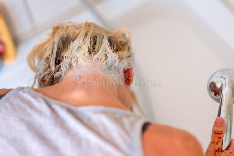 Blonde Frau, die ihr Haar in einem Becken shampooing ist lizenzfreies stockbild