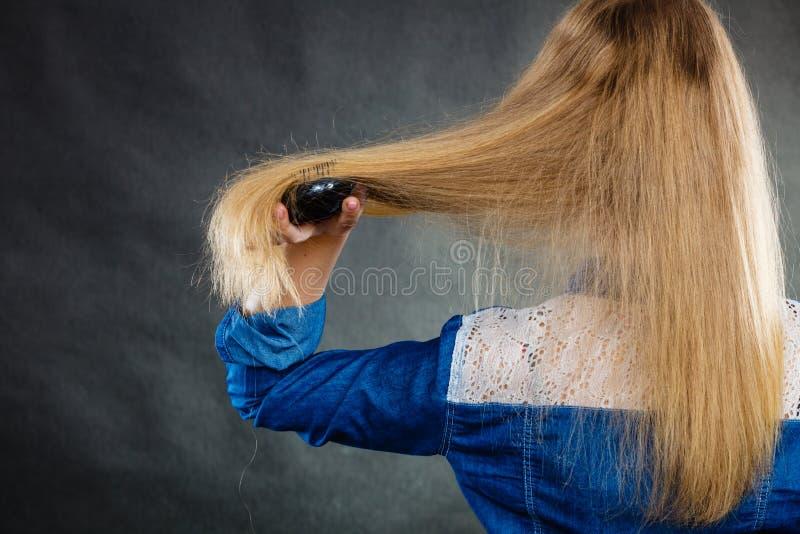 Blonde Frau, die ihr Haar kämmt stockbild