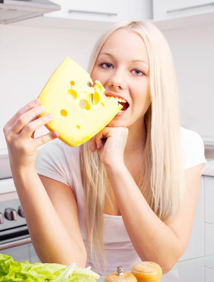 Blonde Frau, die Käse isst stockbilder