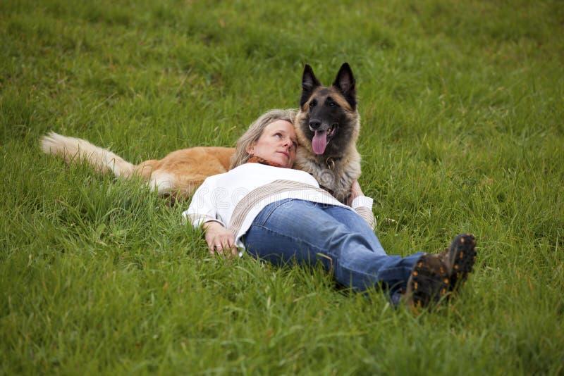 Blonde Frau, die mit ihrem Hund entspannt stockfoto