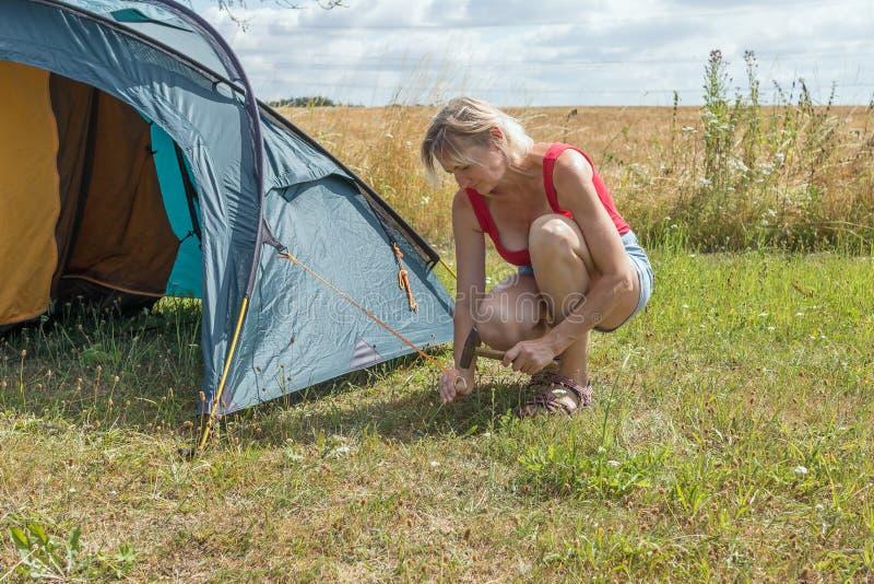 Blonde Frau errichtet Zelt im Freien stockfoto