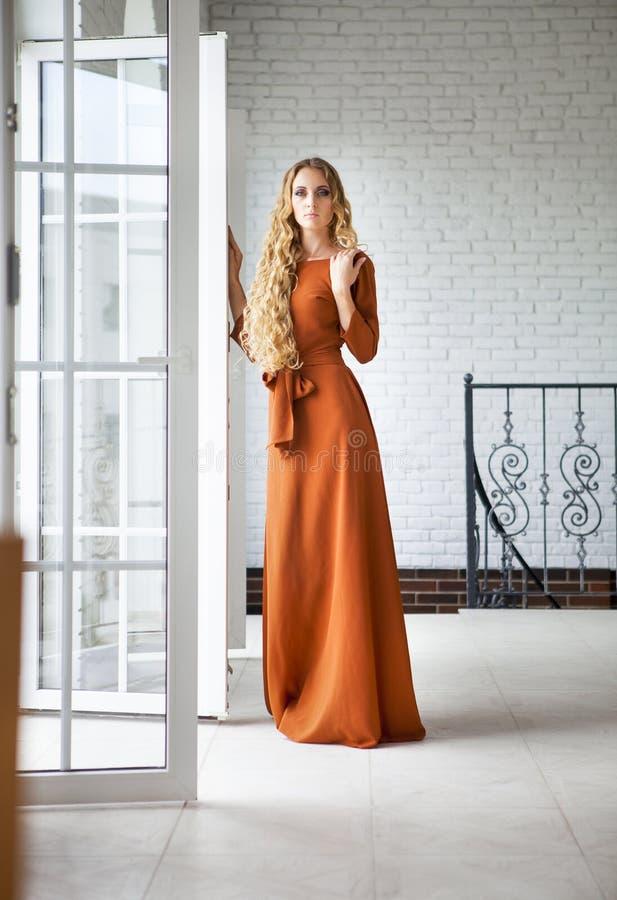 Blonde Frau im langen Kleid nahe der Treppe stockfoto