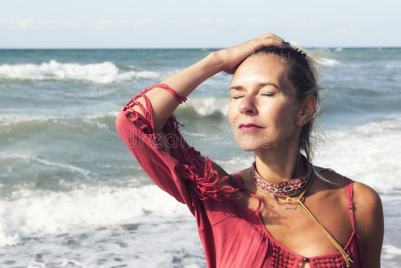 Blonde Frau im roten Kleid, das den Ozean bereitsteht stockfoto