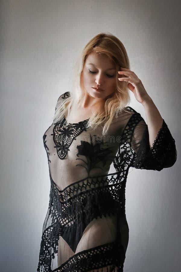 Blonde Frau im schwarzen transparenten Kleid stockbild