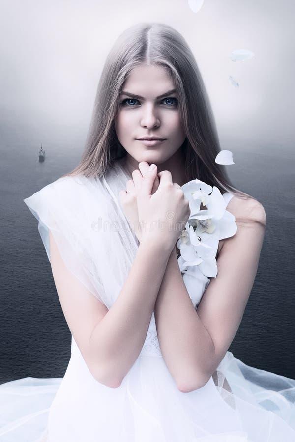 Blonde Frau im Weiß und im Meer lizenzfreie stockbilder