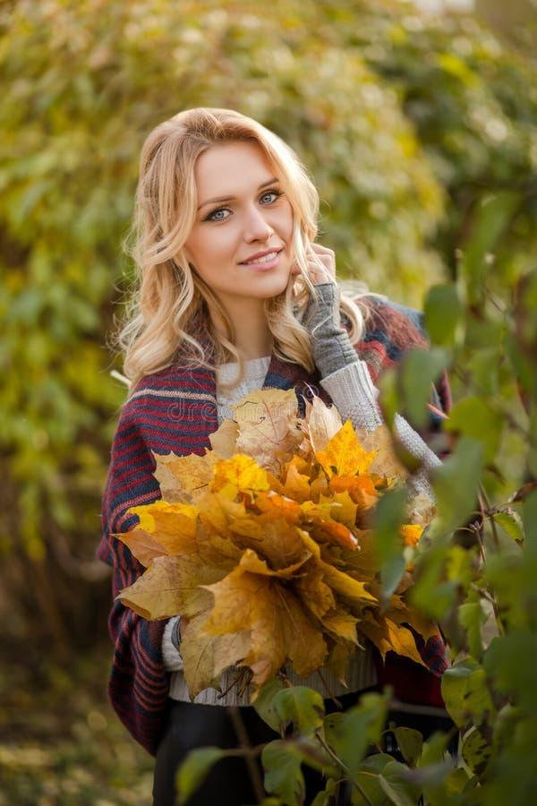 Blonde Frau mit Blumenstrauß von den Ahornblättern stockfoto