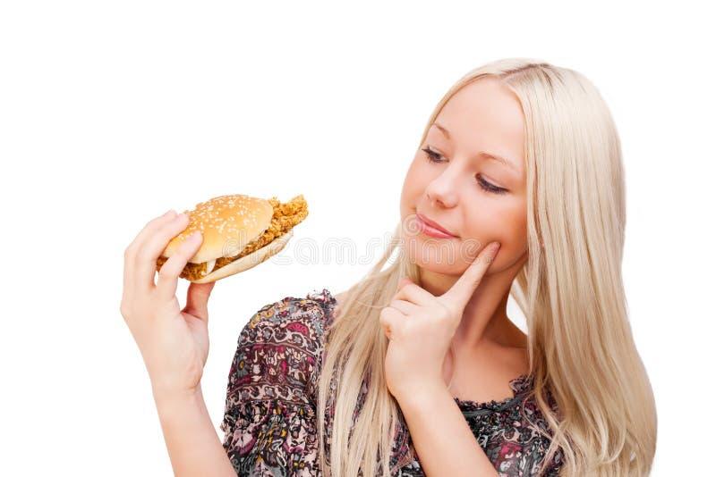 Blonde Frau mit einem Burger stockbilder