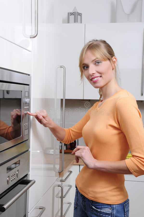 Blonde Frau mit einer Mikrowelle stockfotos