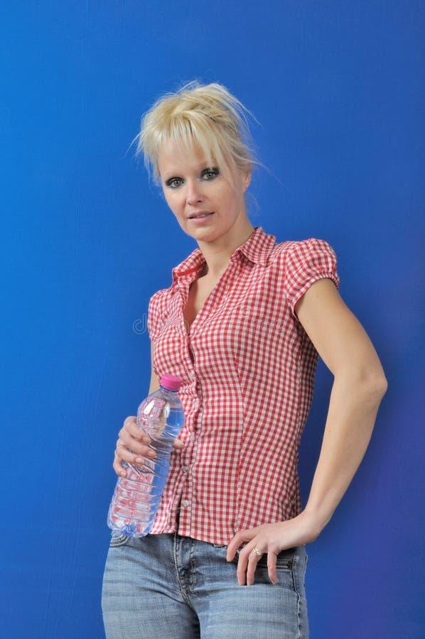 Blonde Frau mit Flasche Wasser stockfoto