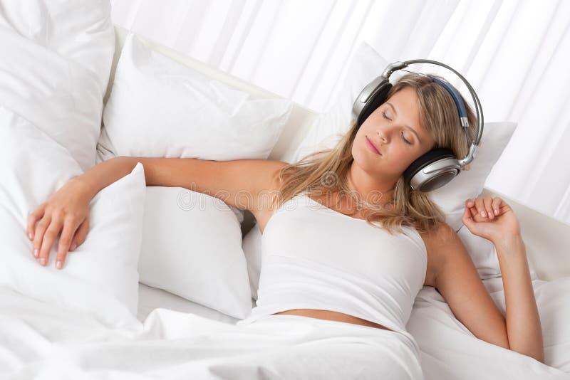 Blonde Frau mit Kopfhörern hörend Musik stockfotografie