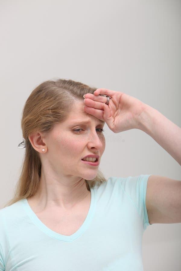 Blonde Frau mit Kopfschmerzen lizenzfreies stockfoto