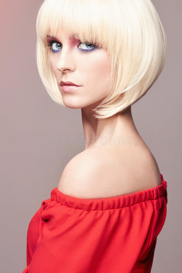 Blonde Frau mit Pendelfrisur, Make-up, rotes Kleid stockbilder