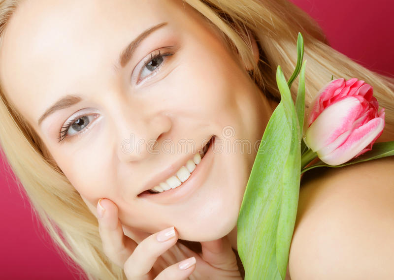 Blonde Frau mit rosa Tulpe stockfoto