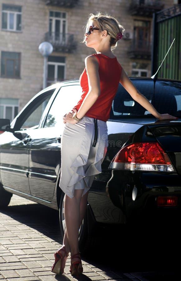 Blonde Frau nahe schwarzem Automobil stockfoto