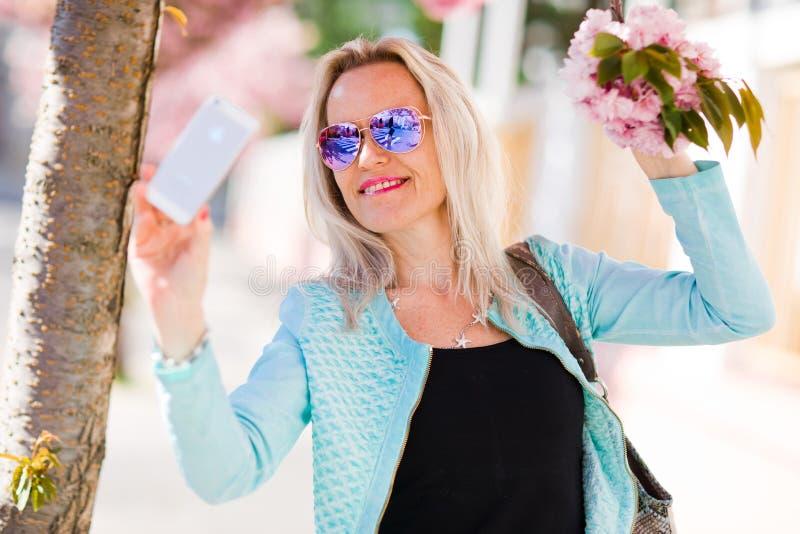 Blonde Frau unter der Kirschblüte, die selfie nimmt stockbild