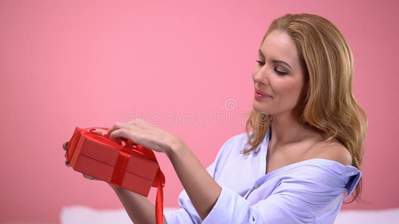 Blonde Frauenöffnungsgeschenkbox mit Valentinsgrußtagesgeschenk, romantische Überraschung stockfotografie