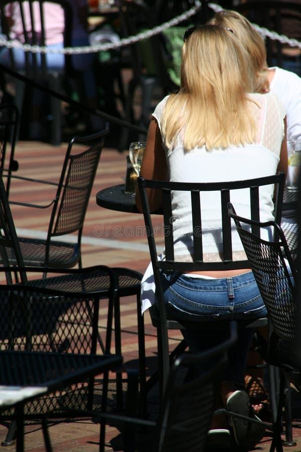 Blonde Frauen, die im im Freiencafé sprechen stockbild