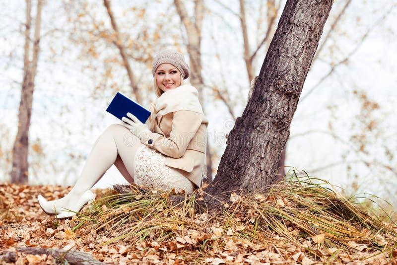 Blonde Frauenlesung im Park stockfoto