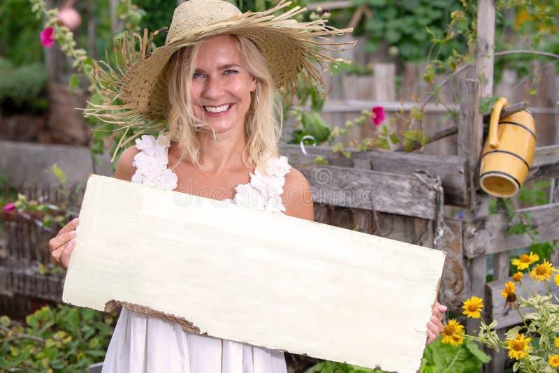 Blonde Frauenstellung im Garten und Halten eines Holzschildes stockbilder