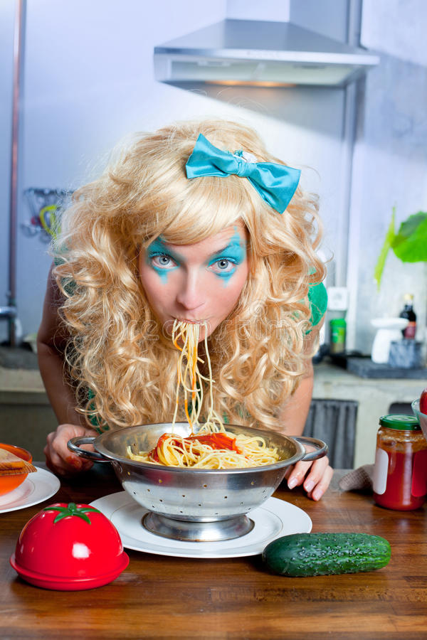 Blonde funny on kitchen eating pasta like crazy. Blonde funny girl on kitchen eating pasta like crazy with blue makeup stock photo
