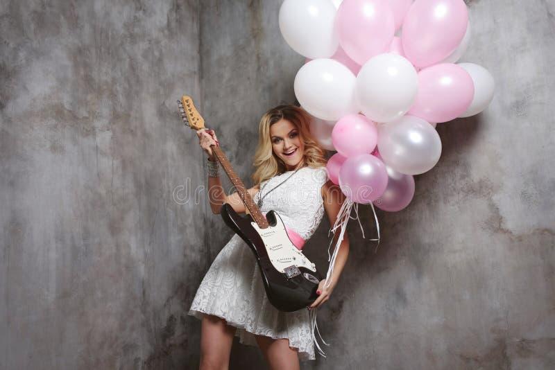 Blonde gaie avec la guitare électrique et les ballons Refroidissez pour passer le temps à la partie images stock