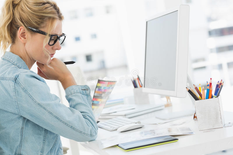 Blonde geconcentreerde ontwerper die bij haar bureau werken stock afbeeldingen