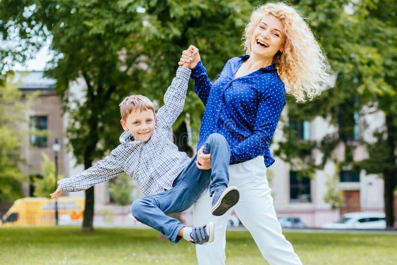 Blonde gelockte Mutter im blauen Hemd und ihrem im Sohn, die Qualitätszeit am Park, Mutter oben wirft ihren Sohn, kaukasische Mut stockfoto