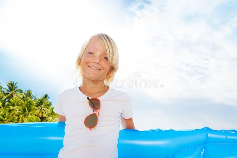 Blonde gelukkige jongen met matras op het strand stock foto