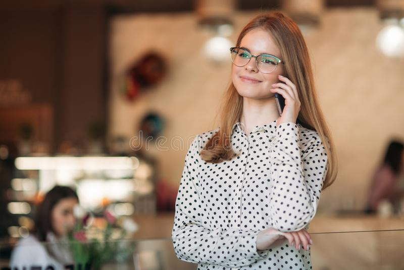 Blonde Geschäftsdame mit glasess benutzen Telefon im Café lizenzfreies stockbild