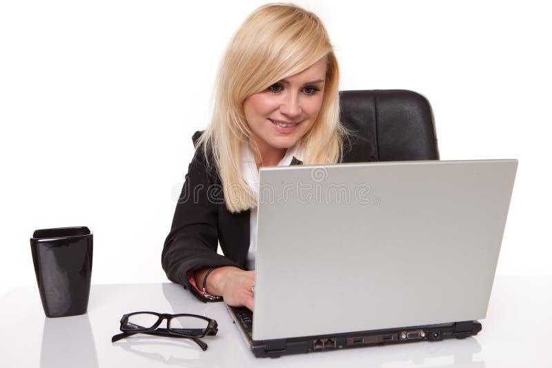 Blonde Geschäftsfrau, die auf ihrem Mobile plaudert stockbilder