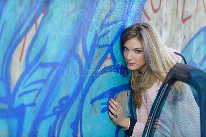 Blonde girl against graffiti wall royalty free stock photo