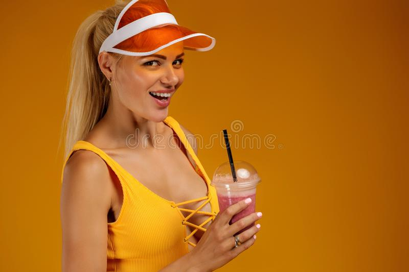 Blonde girl in a bathing suit and hat holding a cocktail. Portrait of blonde girl in bathing suit and hat holding a fresh juice on orange background. healthy royalty free stock photo