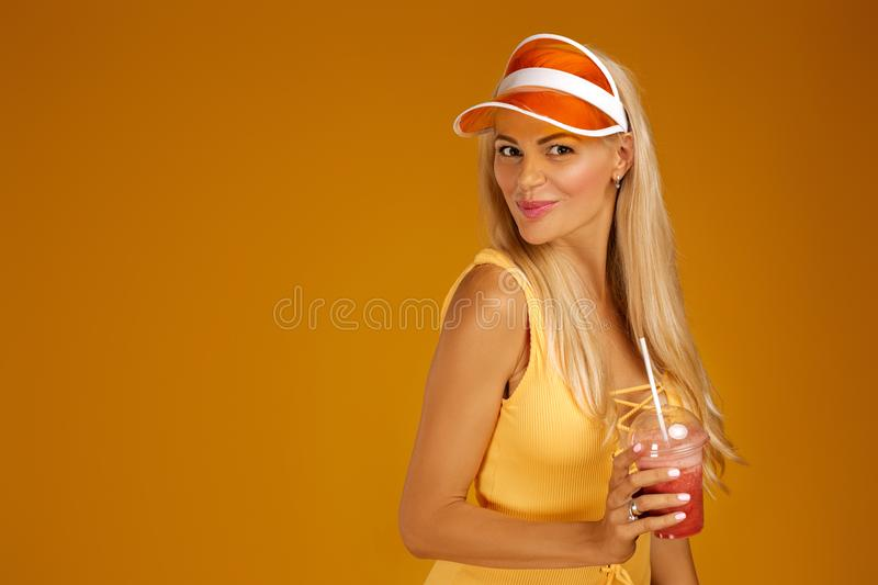 Blonde girl in a bathing suit and hat holding a cocktail. Portrait of blonde girl in bathing suit and hat holding a fresh juice on orange background. healthy stock image