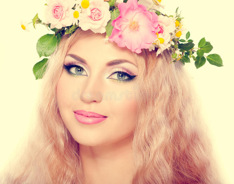 Blonde girl. Beautiful woman with bright makeup and blonde long hair, with flowers stock image