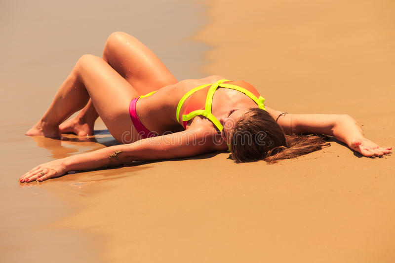Blonde girl in bikini upside view lies on back on wet sand royalty free stock photography