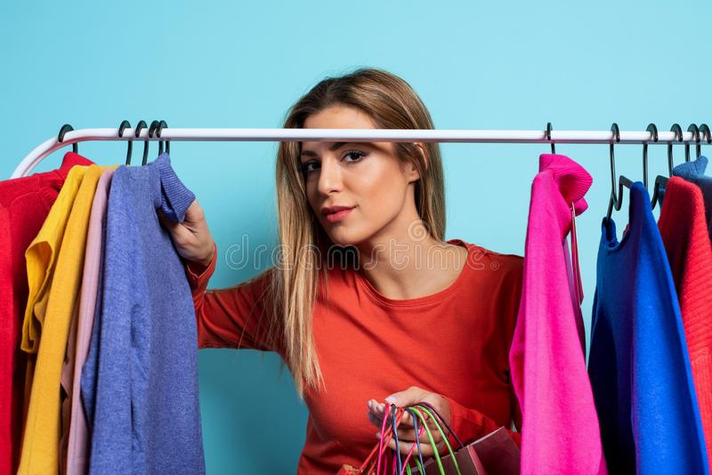 Blonde girl chooses the clothes to buy in a store. Concept of shopping and shopaholic royalty free stock photos
