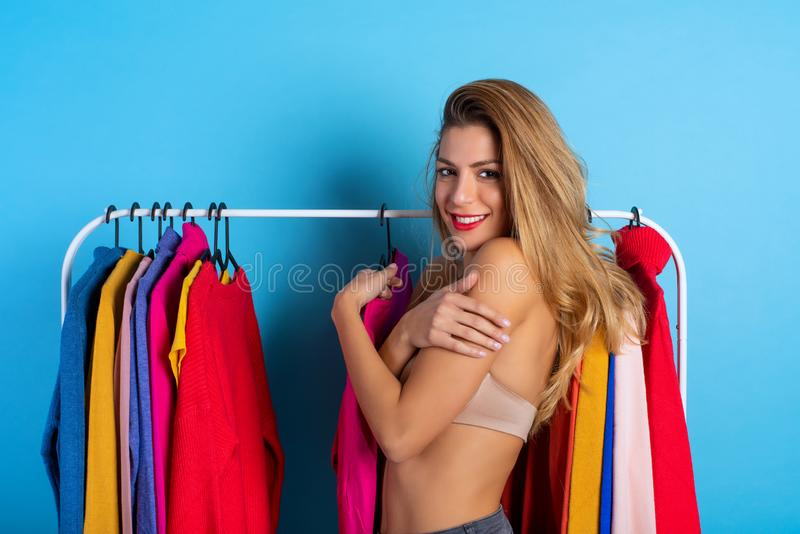 Blonde girl chooses the clothes to buy in a store. Concept of shopping and shopaholic royalty free stock images
