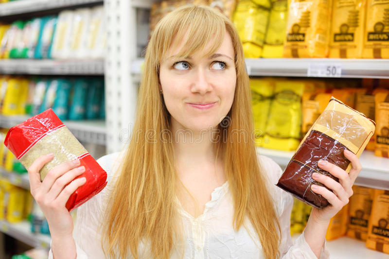 Blonde girl chooses rice in store stock photography