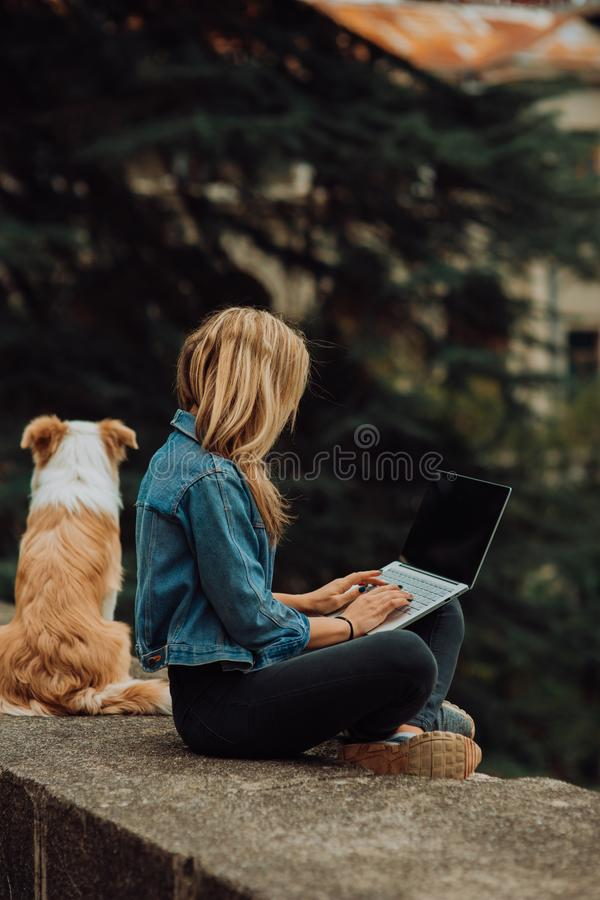 Blonde Girl in cool jeans jacket checking something on her laptop, while sitting in the park with her dog stock images