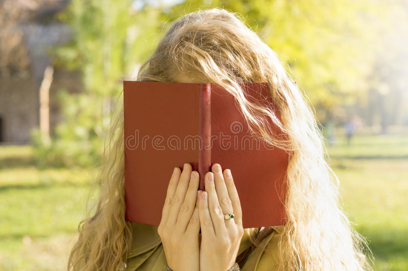 Book Covering Face : Blonde girl covering face with a book stock photo image