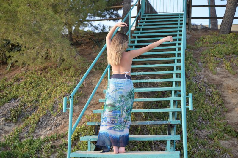 Blonde girl dances on stairs back to the camera and raises and move apart her arms royalty free stock photos