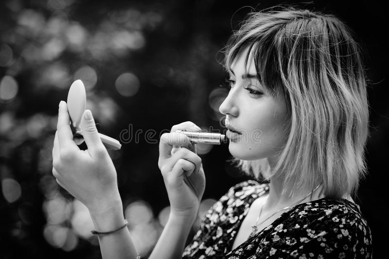 Blonde girl doing makeup on nature, unity with nature and beauty, healthy lifestyle black and white photo. stock photo