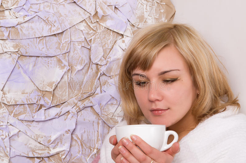 Blonde girl drinks tea from a white cup royalty free stock images