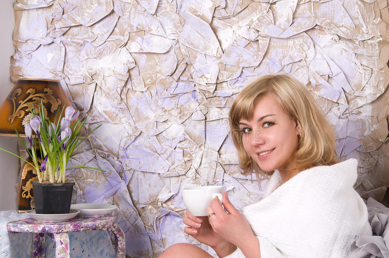 Blonde girl drinks tea from a white cup stock images