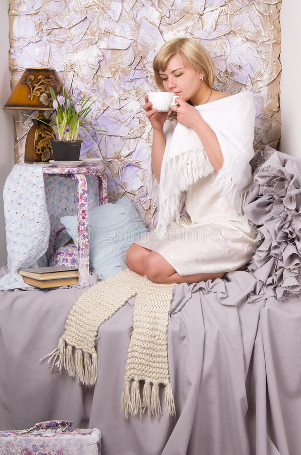 Blonde girl drinks tea from a white cup stock photography