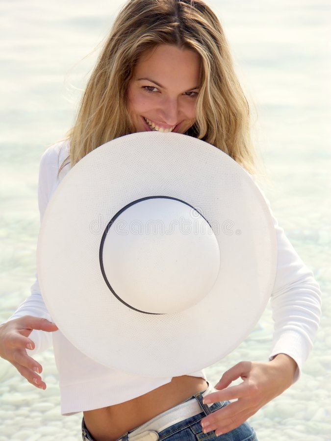 Blonde girl eating white hat stock photography