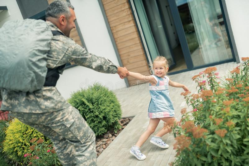 Blonde girl feeling unhappy while father leaving for half a year. Father leaving. Blonde girl feeling unhappy while father serving as military men leaving for royalty free stock photos