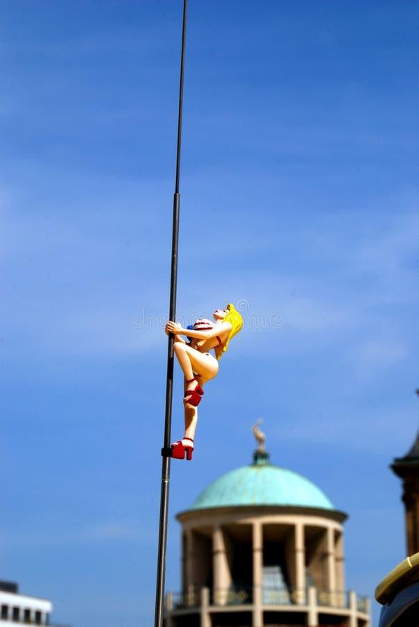 Blonde girl figurine climbing straight up stock photo