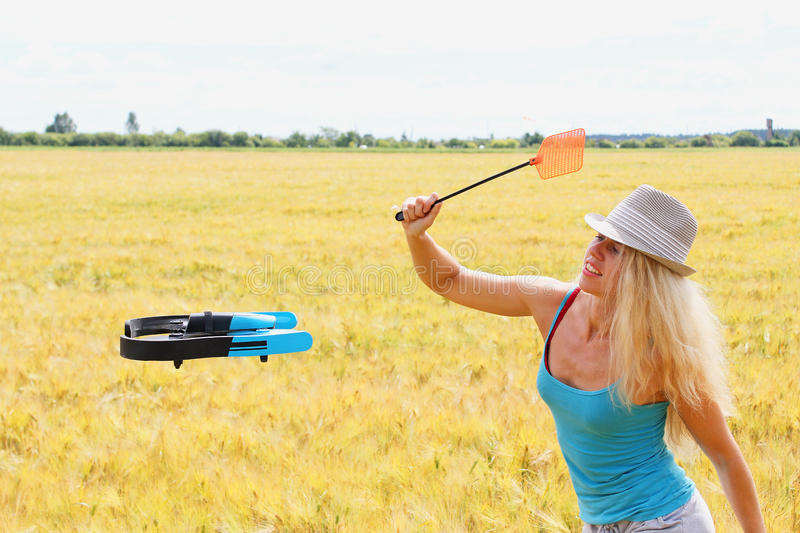 The blonde girl with a fly swatter drives away drone. The blonde girl in white hat with a fly swatter drives away drone, against wheat field stock image