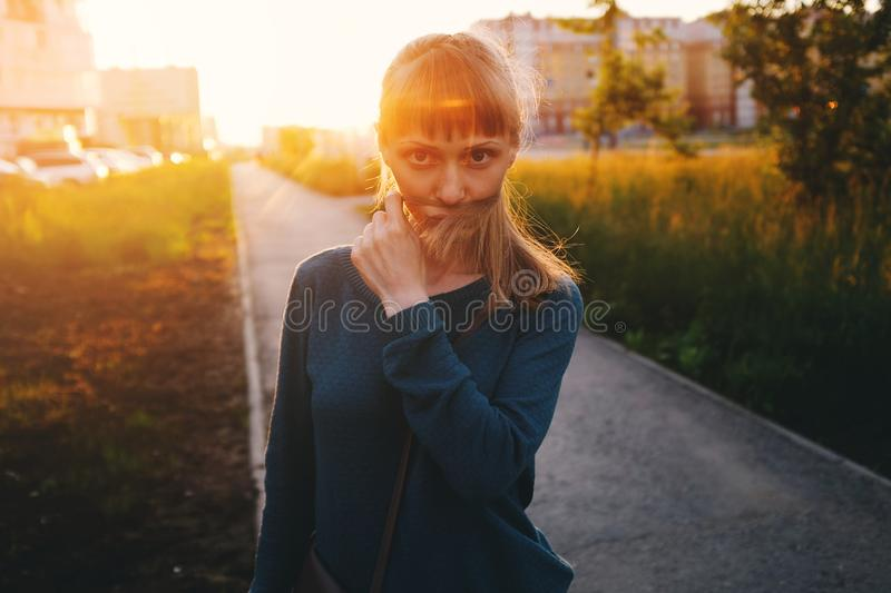 Blonde girl fooling around with long hair, walking on a Sunny summer day, against the background of houses and trees. A young stock photography
